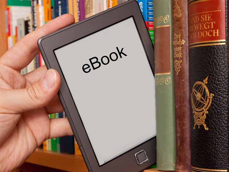 A hand removing an ebook reader from a shelf full of printed books
